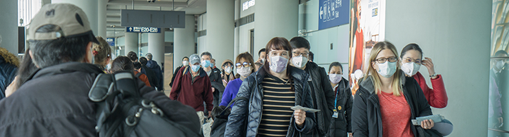 travelers in airport wearing masks to prevent coronavirus